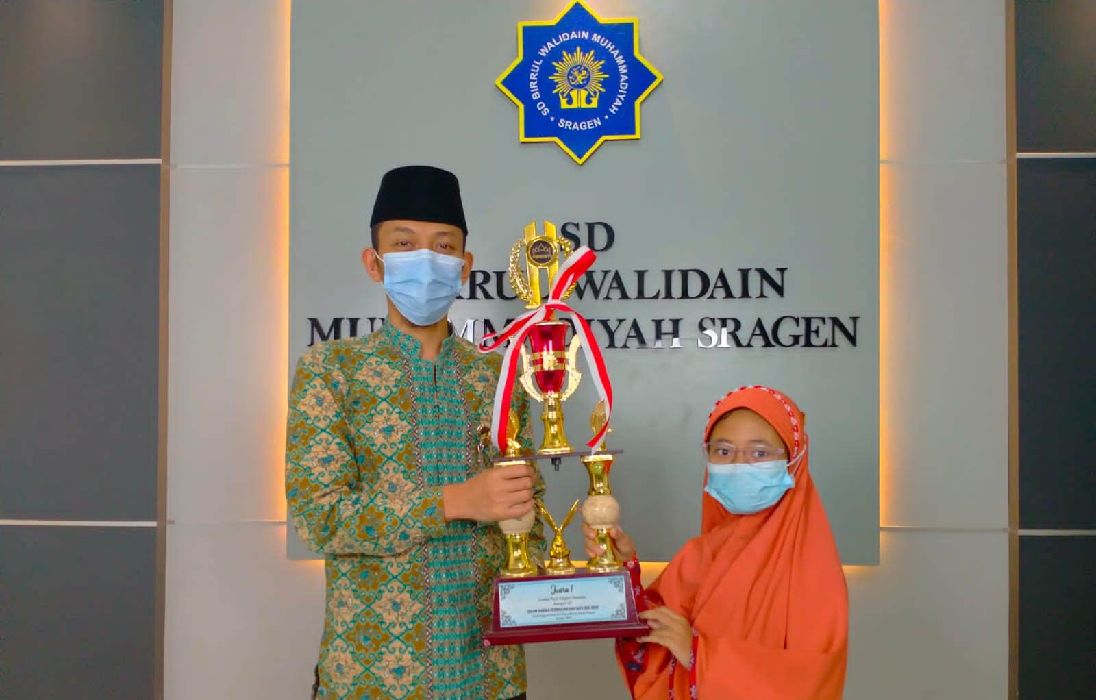 MEMBANGGAKAN: Larasnissa Wandan Nilam Kusumastuti (kiri) bersama Kepala Sekolah SD Birul Walidain Annas Sayidina (kanan) saat menunjukkan trofi. (MUKHTARUL HAFIDH/LINGKARJATENG.CO.ID)